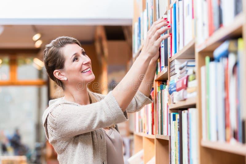 Mulher que escolhe o livro na livraria fotografia de stock