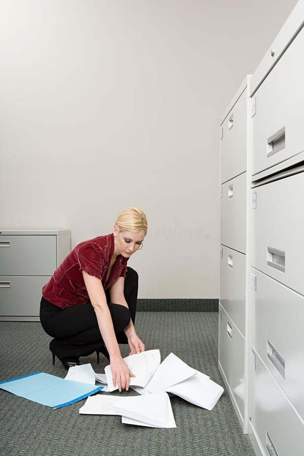 Mulher que escolhe o papel acima deixado cair imagem de stock royalty free