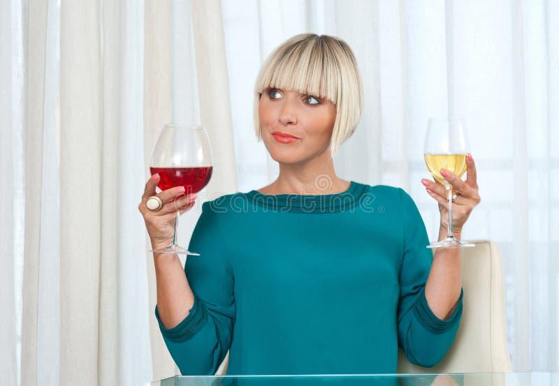 Mulher que escolhe o vinho vermelho e branco betwean imagem de stock