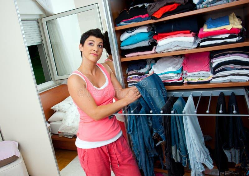 Mulher que escolhe a roupa foto de stock