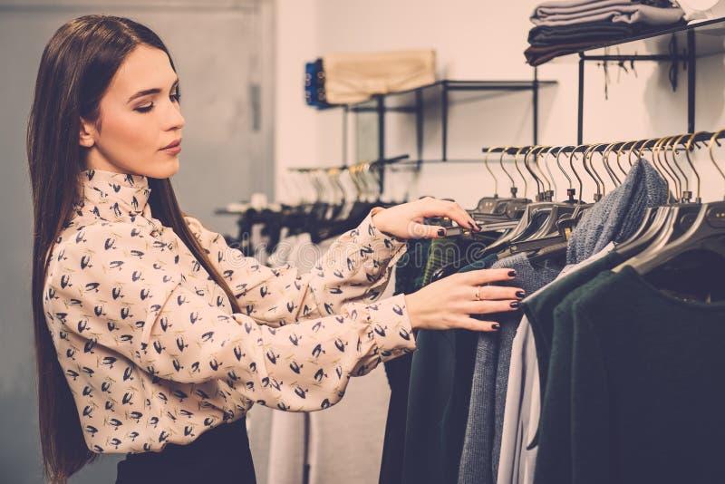 Mulher que escolhe a roupa em uma sala de exposições fotografia de stock