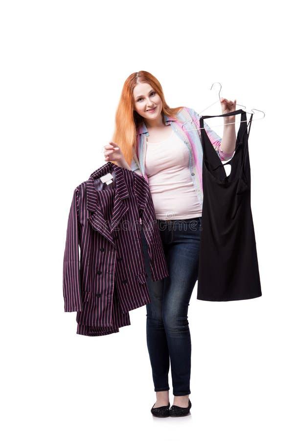 A mulher que escolhe a roupa na loja isolada no branco imagem de stock