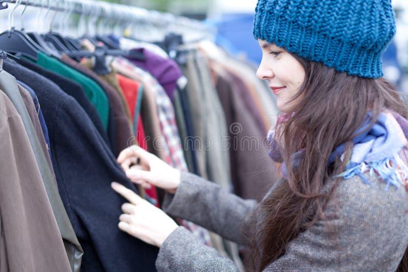Mulher que escolhe a roupa no mercado de pulga. imagem de stock