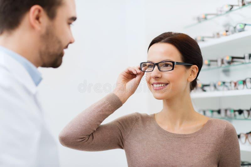 Mulher que escolhe vidros na loja do sistema ótico imagens de stock