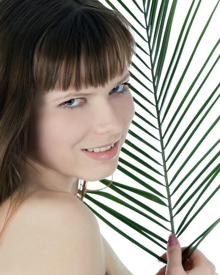Mulher que esconde atrás da folha de palmeira grande imagem de stock royalty free
