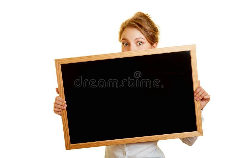 Mulher que esconde timidamente atrás do quadro-negro imagem de stock royalty free