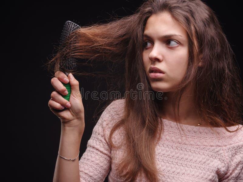 Mulher que escova o cabelo tangled com um pente em um fundo preto Menina que olha o cabelo doente danificado Conceito dos problem fotografia de stock royalty free