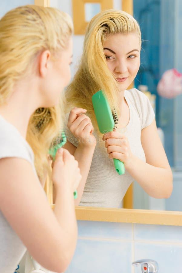 Mulher que escova seu cabelo louro no banheiro imagem de stock royalty free