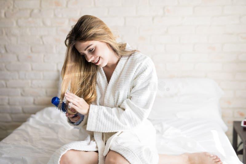 Mulher que escova seu cabelo na cama imagens de stock