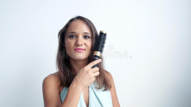 Mulher que escova seu cabelo saudável com escova Fêmea nova com olhares marrons longos retos dos cabelos da beleza na câmera e fotografia de stock