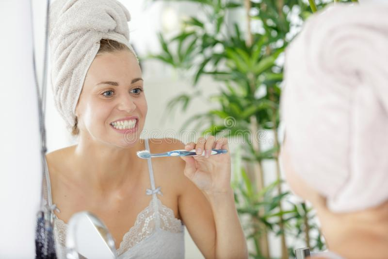 Mulher que escova seus dentes foto de stock
