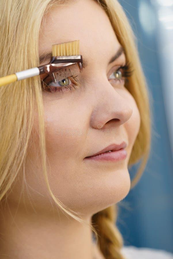 Mulher que escova suas sobrancelhas fotos de stock royalty free