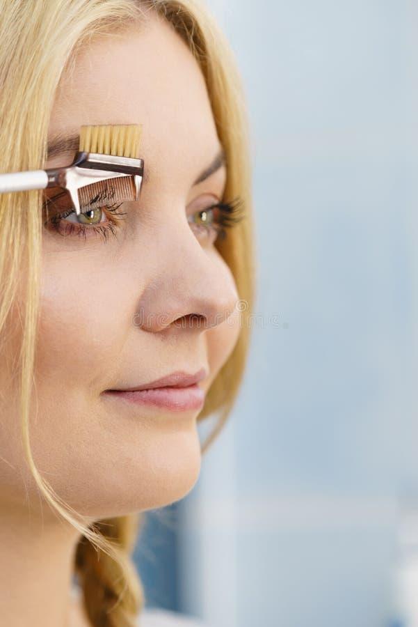 Mulher que escova suas sobrancelhas imagens de stock