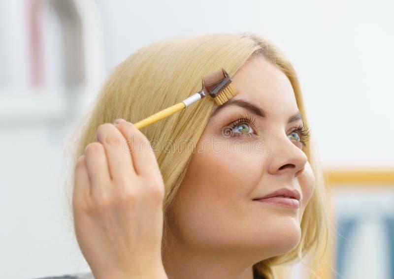 Mulher que escova suas sobrancelhas fotografia de stock