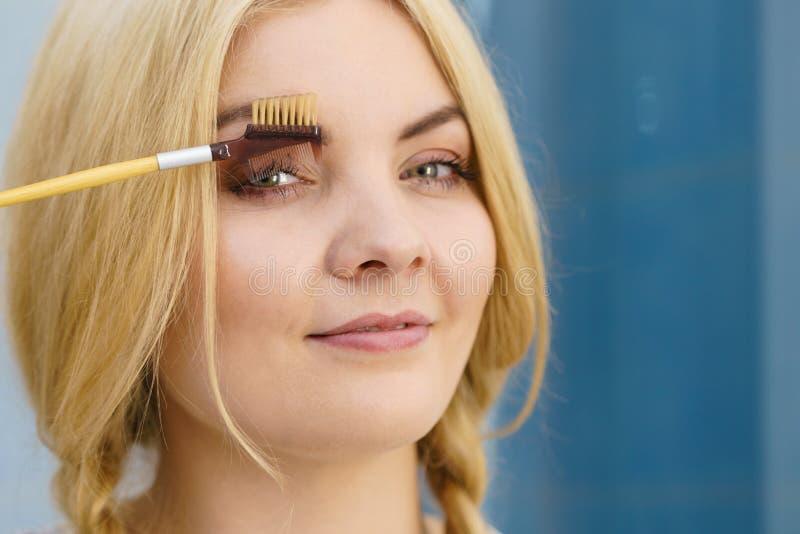 Mulher que escova suas sobrancelhas imagem de stock royalty free