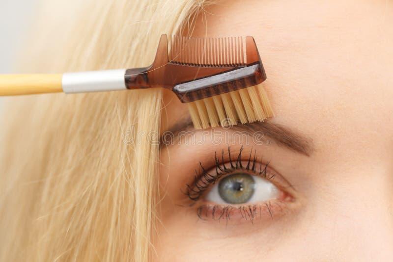Mulher que escova suas sobrancelhas fotos de stock