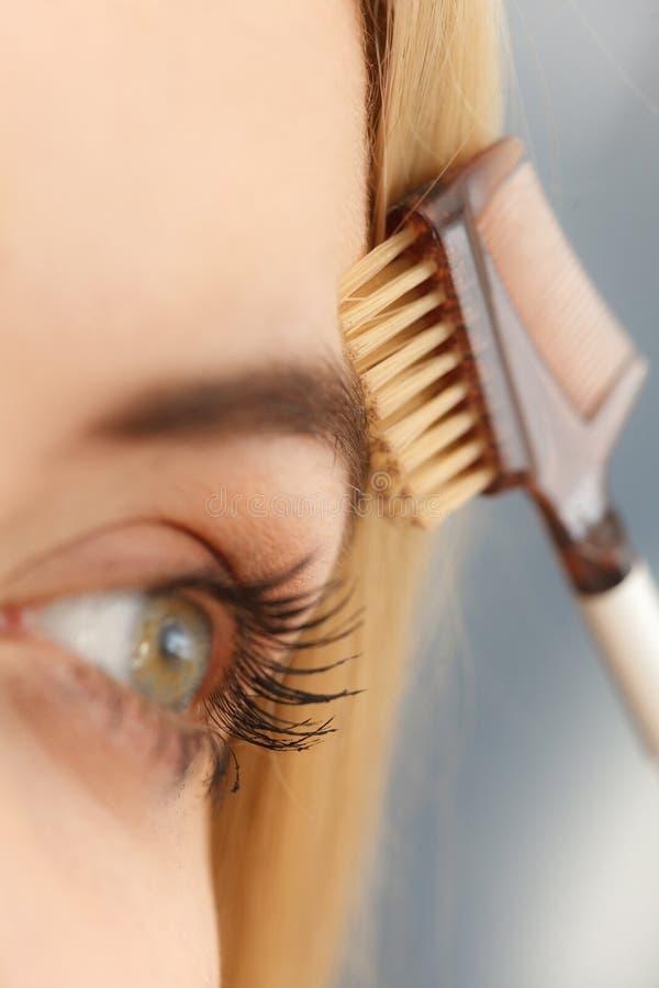 Mulher que escova suas sobrancelhas imagem de stock