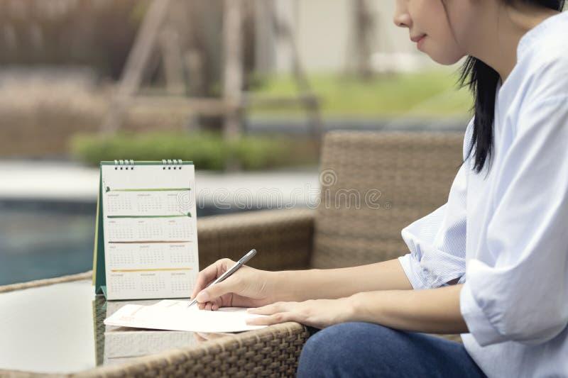 Mulher que escreve o plano no caderno, na agenda planejando e na programação usando o planejador de evento do calendário na mesa  fotografia de stock