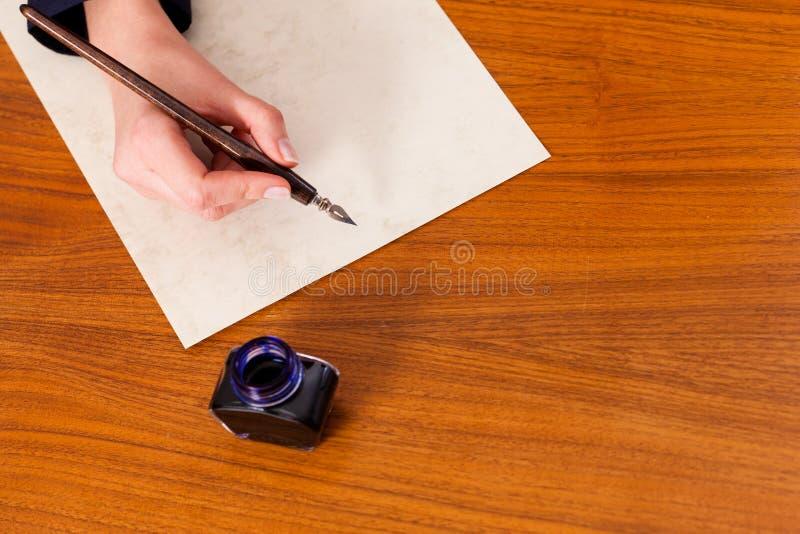 Mulher que escreve uma letra com pena e tinta imagens de stock