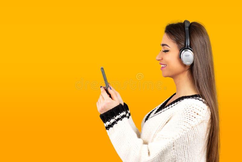 Mulher que escuta a música com os fones de ouvido no telefone celular fotografia de stock royalty free