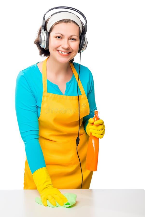 A mulher que escuta a música e faz a limpeza da casa imagens de stock