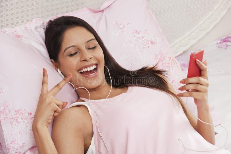 Mulher que escuta a música em um leitor de mp3 imagens de stock