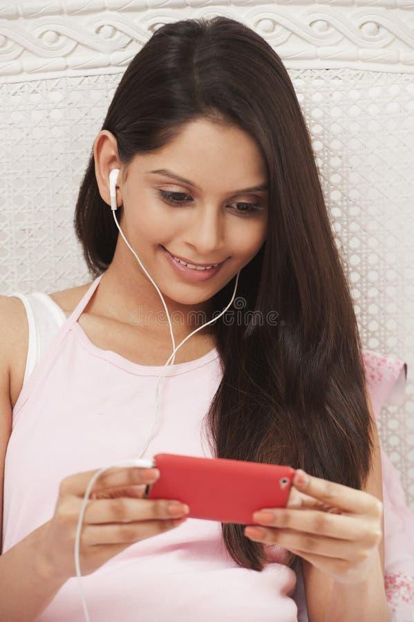 Mulher que escuta a música em um leitor de mp3 foto de stock royalty free