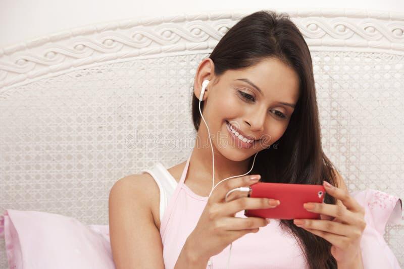 Mulher que escuta a música em um leitor de mp3 fotos de stock royalty free