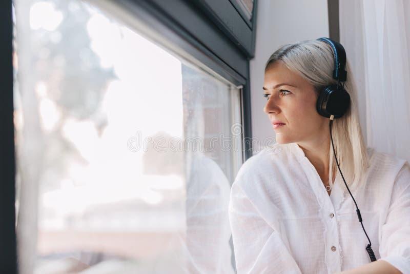 Mulher que escuta a música, olhando através da janela fotografia de stock