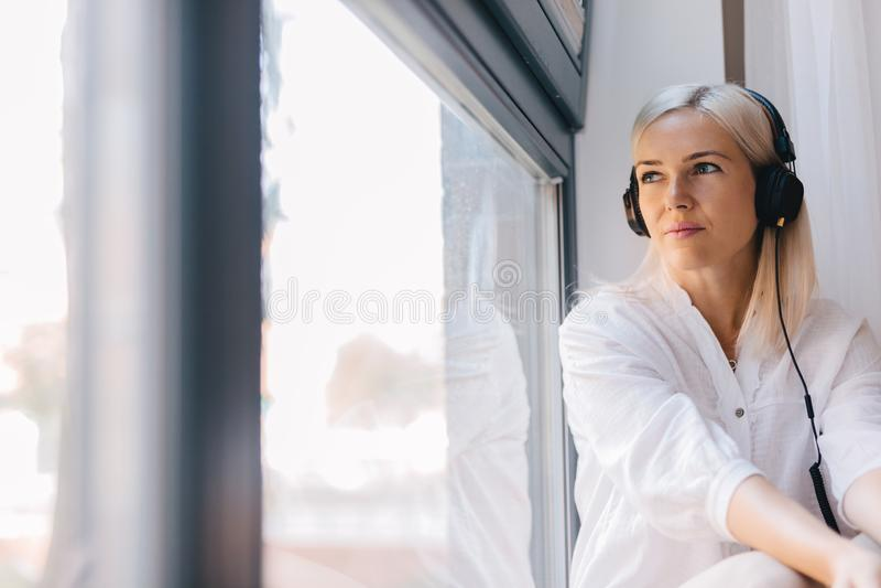 Mulher que escuta a música, olhando fixamente para fora a janela fotografia de stock