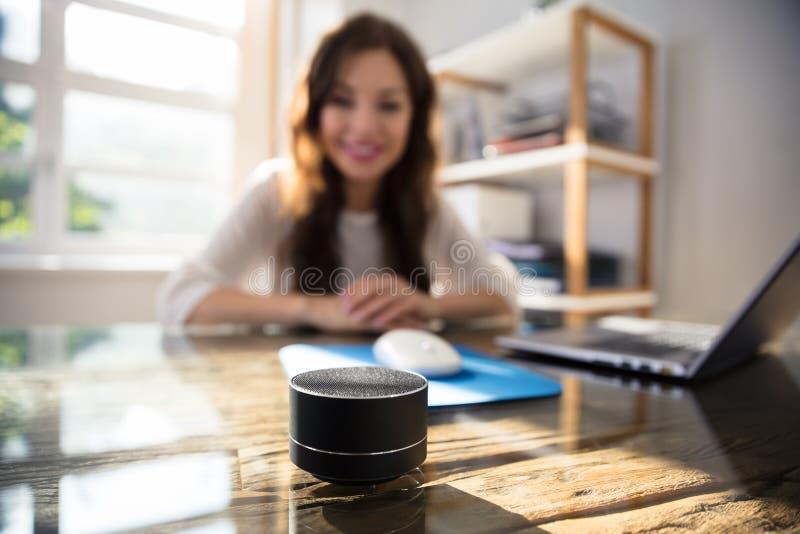 Mulher que escuta a m?sica no orador sem fio fotografia de stock royalty free
