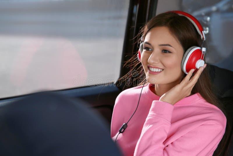 Mulher que escuta o audiobook através dos fones de ouvido imagens de stock royalty free