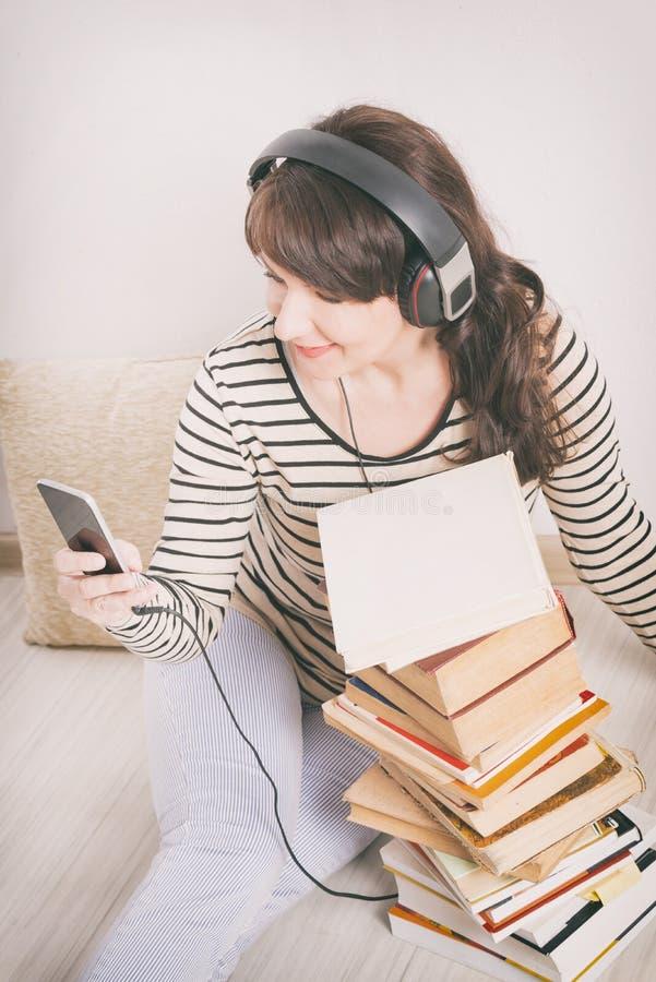 Mulher que escuta um audiobook imagem de stock