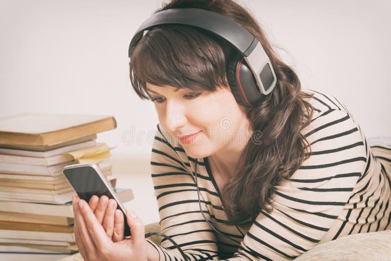Mulher que escuta um audiobook imagens de stock