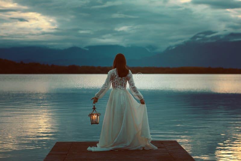 Mulher que espera com lanterna em um cais imagens de stock royalty free