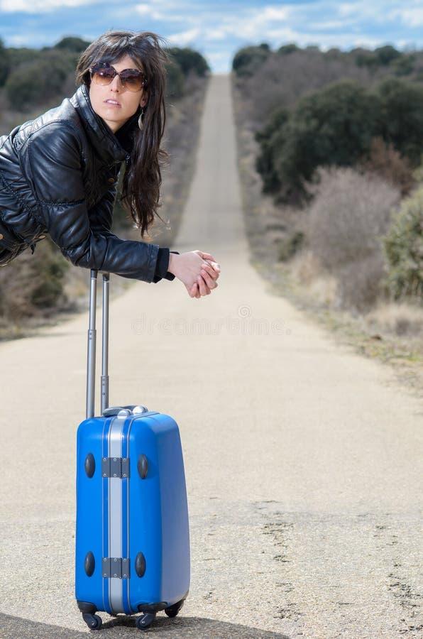 Mulher que espera na estrada com mala de viagem fotos de stock royalty free