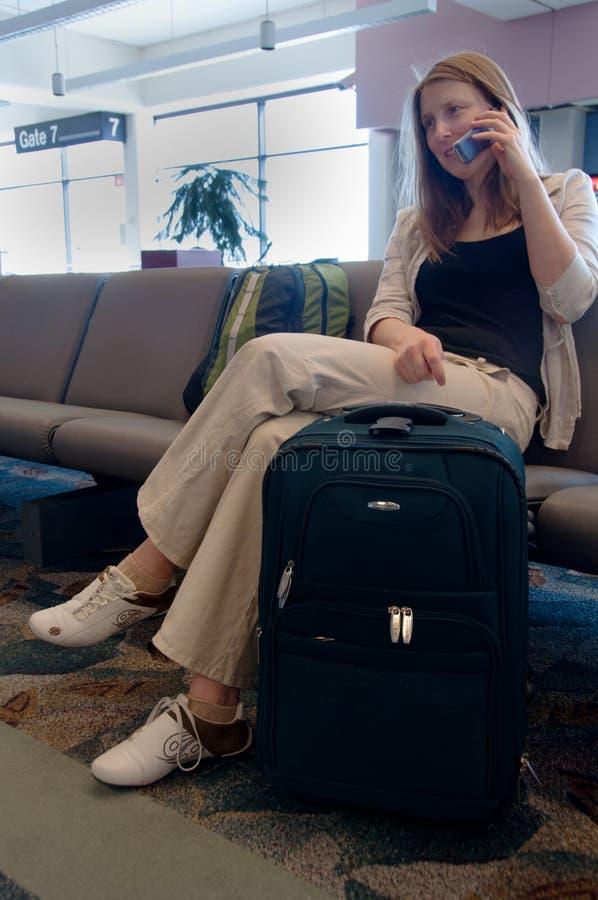 Mulher que espera na porta do aeroporto que fala no telemóvel fotos de stock royalty free