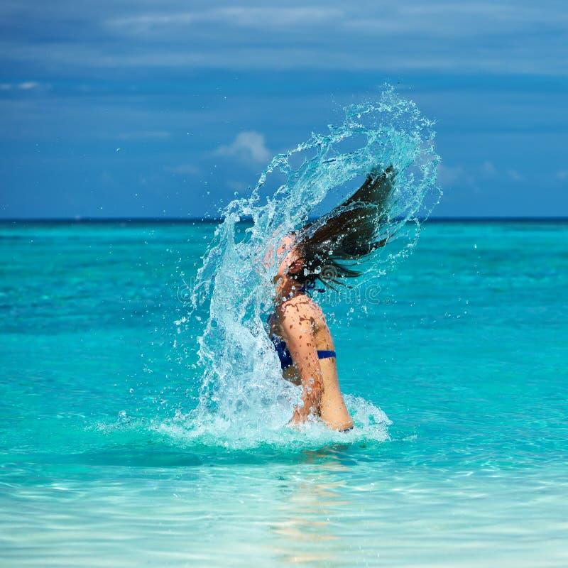 Mulher que espirra a água com o cabelo no oceano fotos de stock