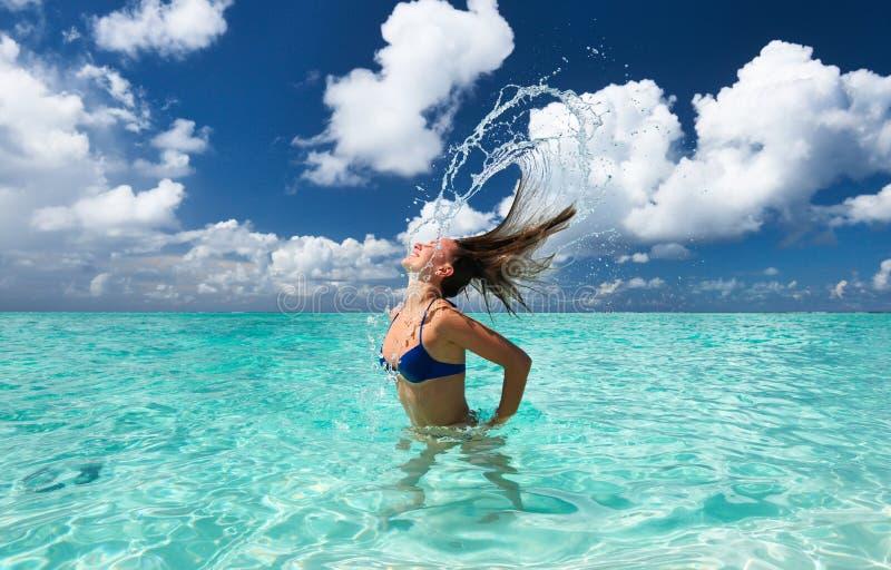 Mulher que espirra a água com o cabelo no oceano foto de stock