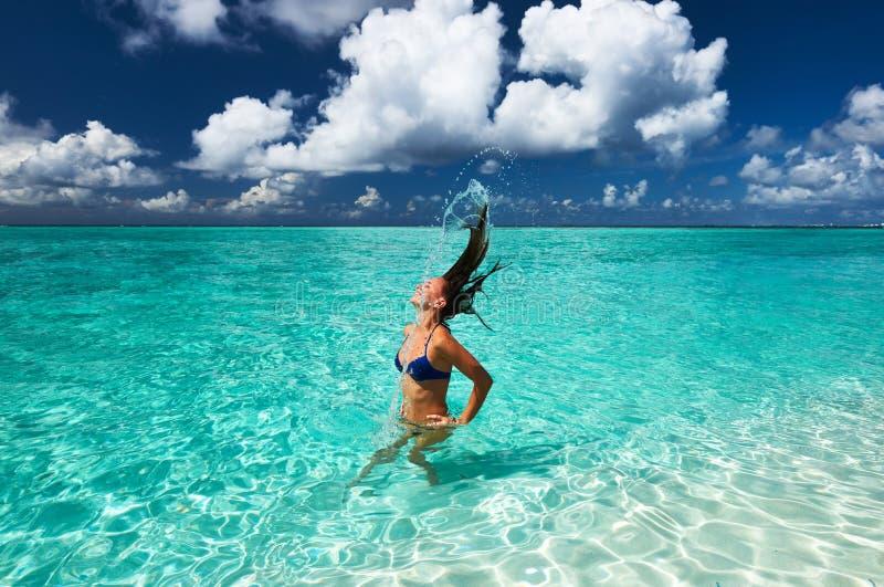 Mulher que espirra a água com o cabelo no oceano fotografia de stock