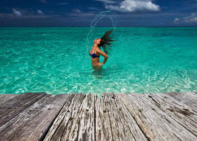 Mulher que espirra a água com o cabelo no oceano fotografia de stock royalty free