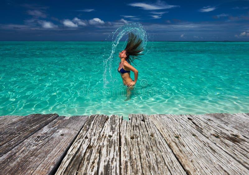 Mulher que espirra a água com o cabelo no oceano imagens de stock
