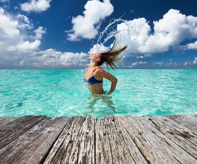 Mulher que espirra a água com o cabelo no oceano imagem de stock royalty free