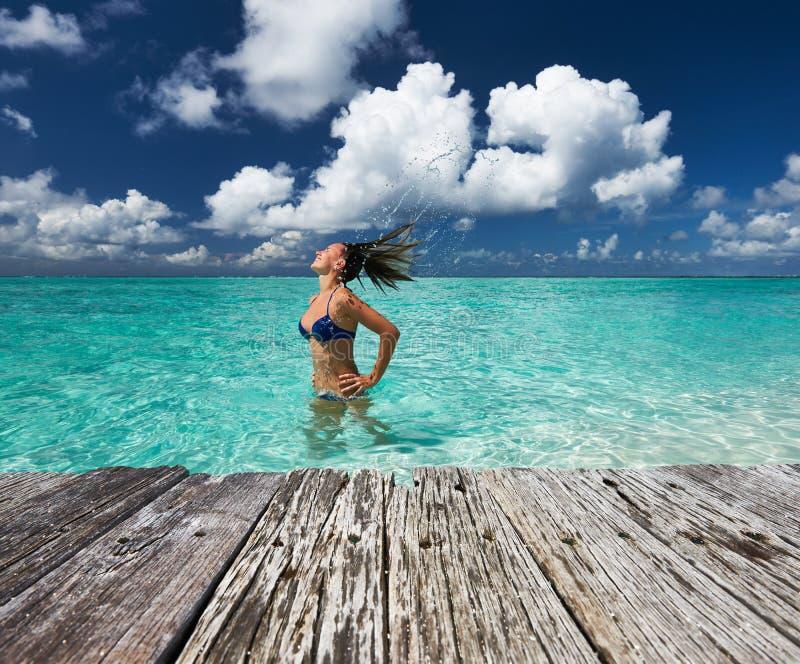 Mulher que espirra a água com o cabelo no oceano imagens de stock royalty free
