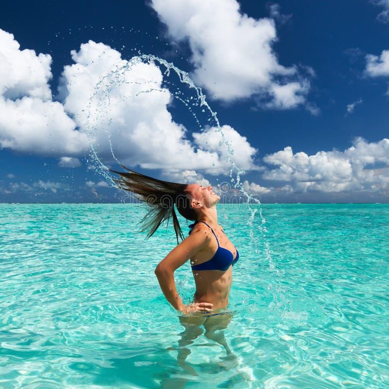 Mulher que espirra a água com o cabelo no oceano foto de stock royalty free