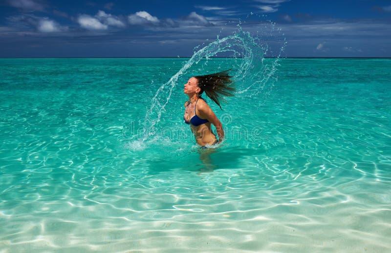 Mulher que espirra a água com o cabelo no oceano fotos de stock royalty free