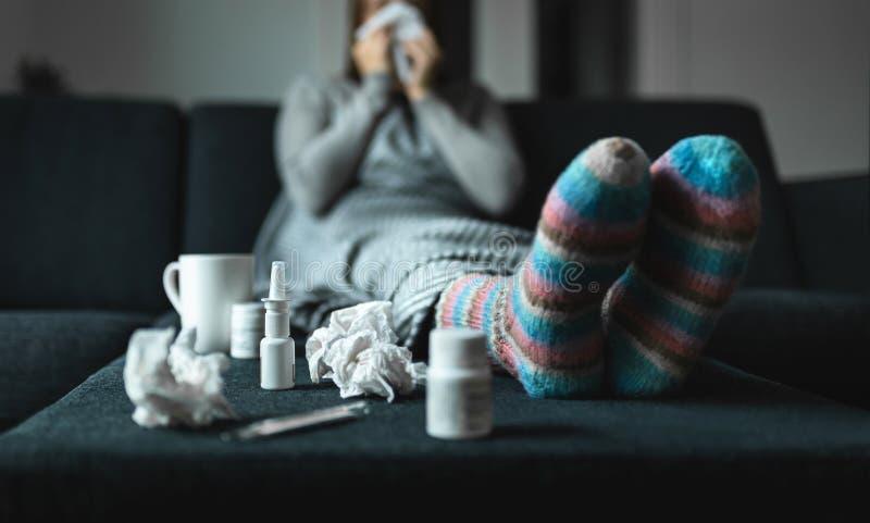 Mulher que espirra e nariz de sopro com tecido e lenço Pessoa doente e doente com gripe, medicina fria e as peúgas de lã imagem de stock