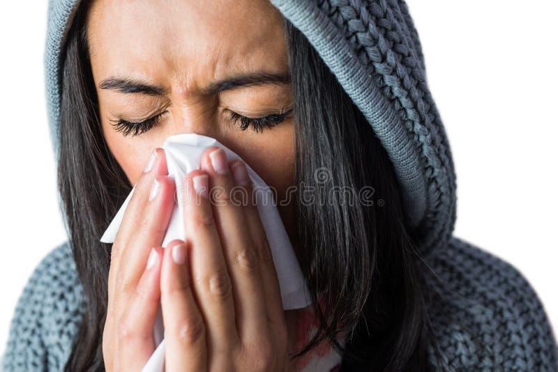 Mulher que espirra em seu tecido fotos de stock