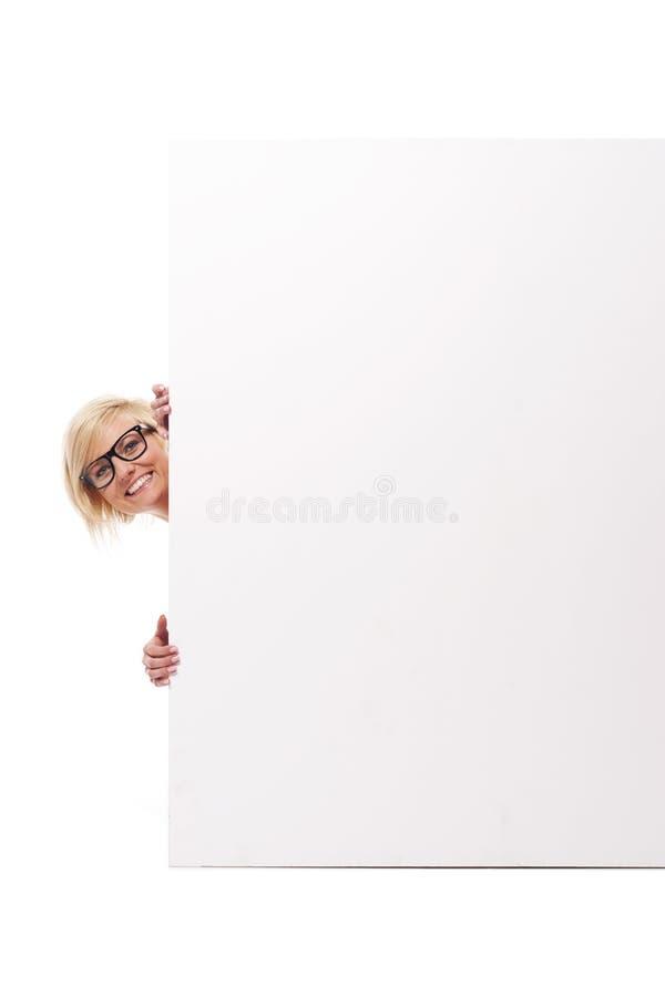 Mulher que espreita atrás da placa imagem de stock