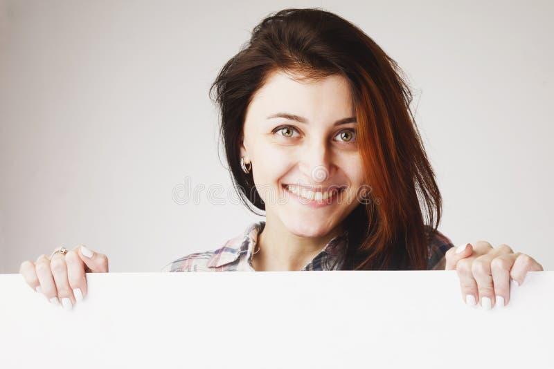 Mulher que espreita atrás de um whiteboard fotografia de stock